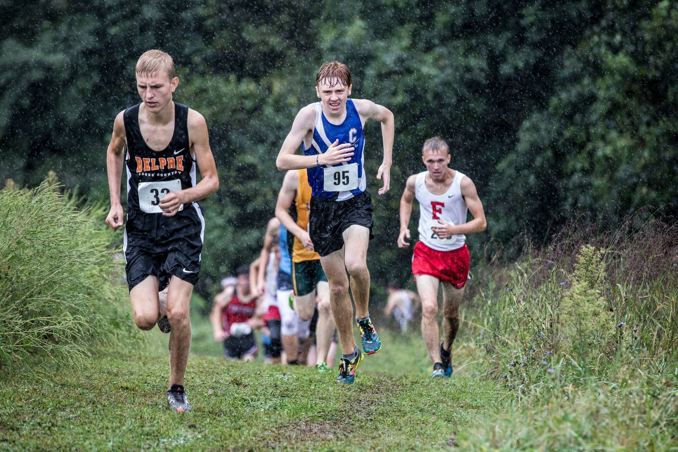 Fighting the rain and the mud, Chillicothe's Andrew McCallum, middle, took second place in one of his first local meets in the boys race during Zane Trace's annual cross-country invitational with a time of 18:02.63.