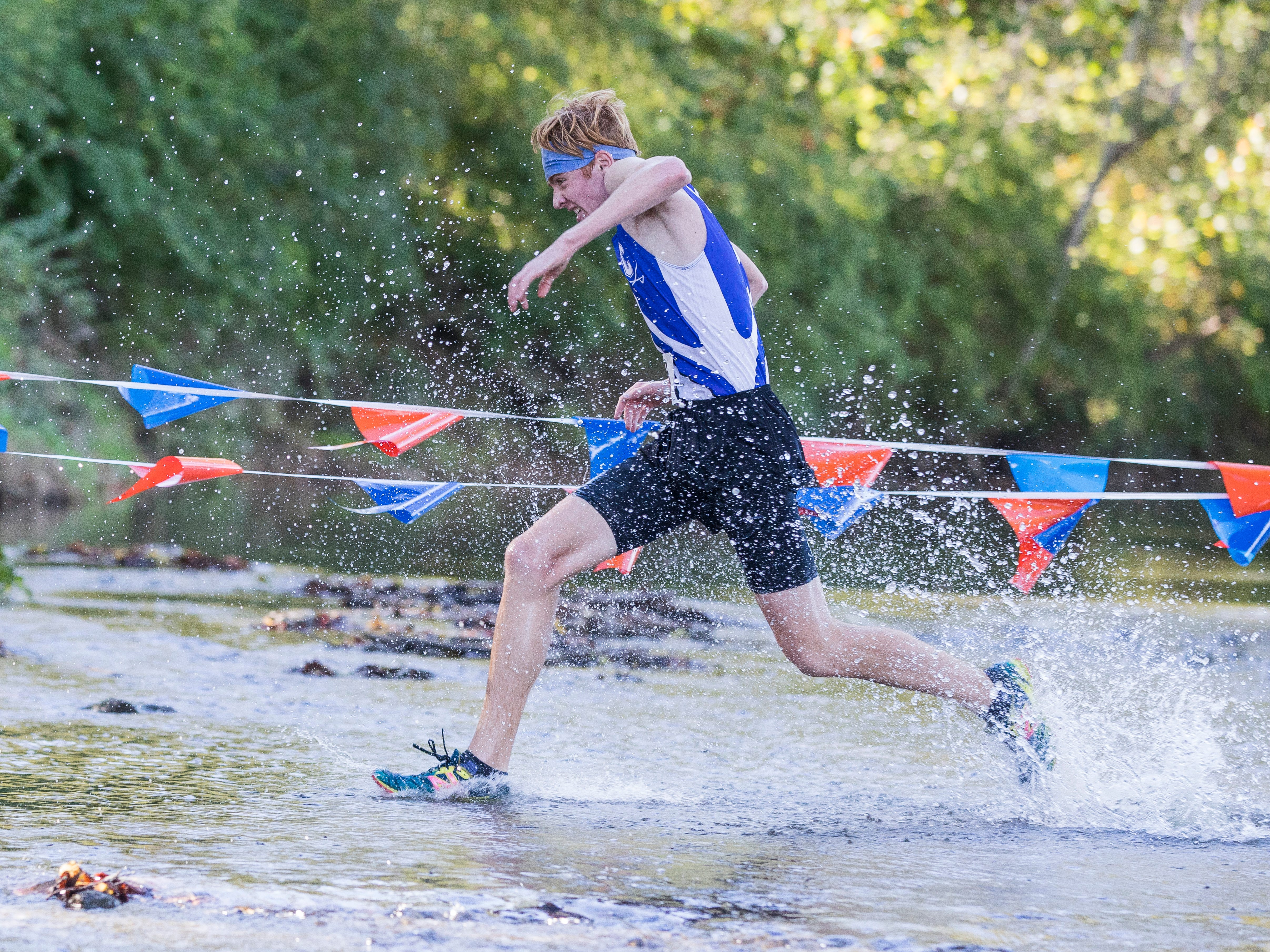 Andrew McCallum runs through Sugar Creek at Beaver Crossing at the 2018 Frontier Athletic Conference cross-country race. Andrew would take first place at the race with a time of 16:48.00 even though, this time last year, Andrew could barely run due to having Guillain-Barre syndrome, a rare disorder in which your body's immune system attacks your nerves.