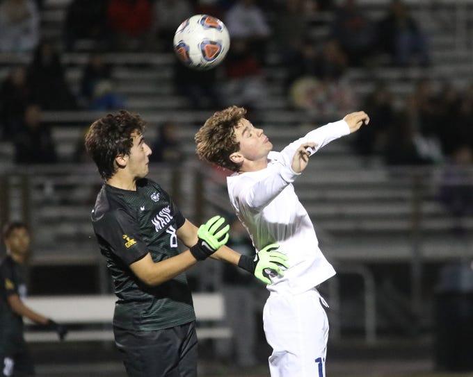 Moeller midfielder Parker Grinstead battles Mason midfielder Sebastian Amaya during their district final.
