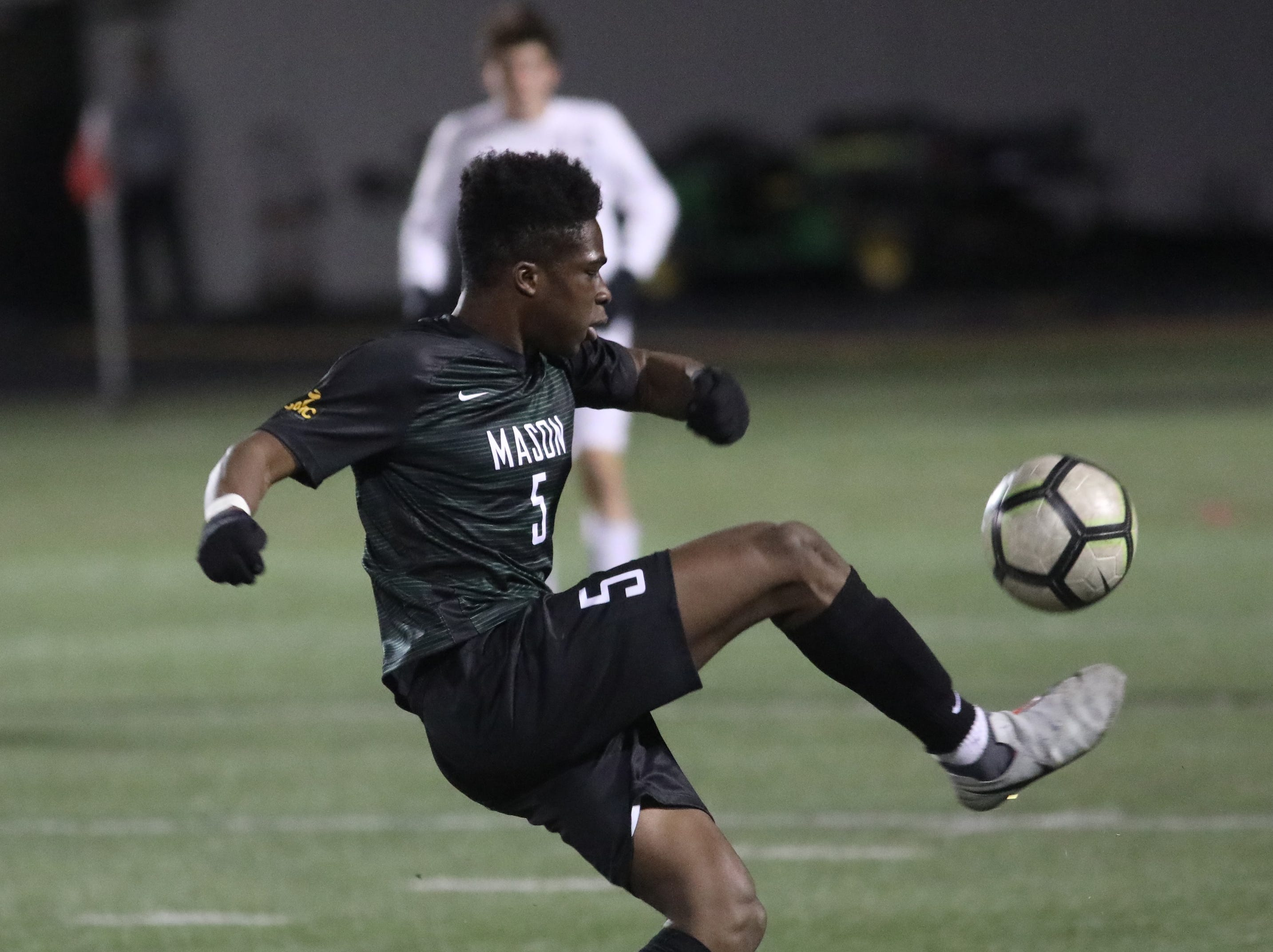 Mason player Bola Adesanya kicks the ball during their district final against Moeller.