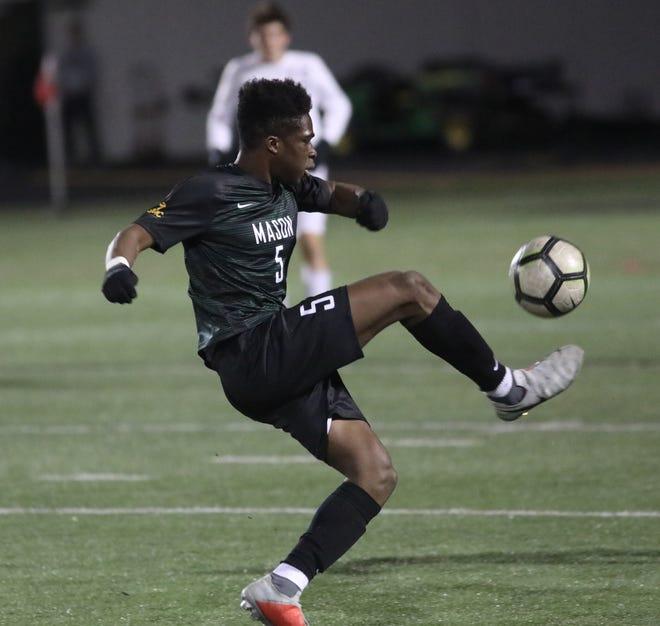 Mason player Bola Adesanya kicks the ball during their district final against Moeller.