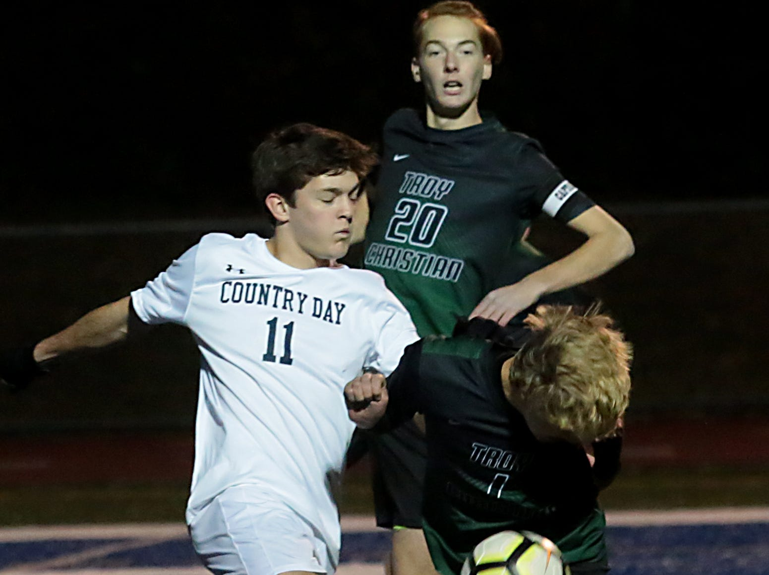 CCD midfielder Riley Michalski tries to clear the ball from Troy Christian defender Chas Shemmel during their Division III district final soccer match at Wyoming Thursday, Oct. 25, 2018.