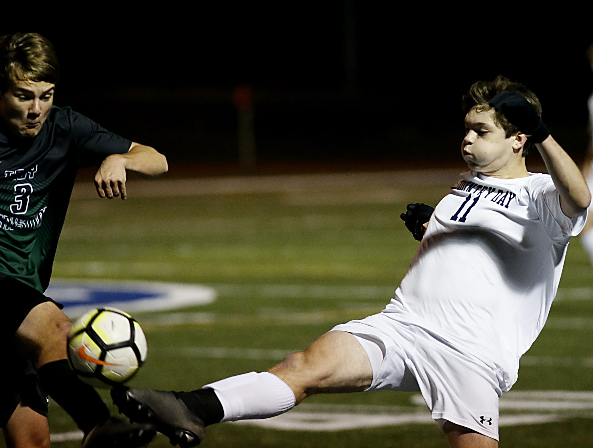 CCD midfielder Riley Michalski gets his foot on the ball before Troy Christian defender Ty Davis during their Division III district final soccer match at Wyoming Thursday, Oct. 25, 2018.