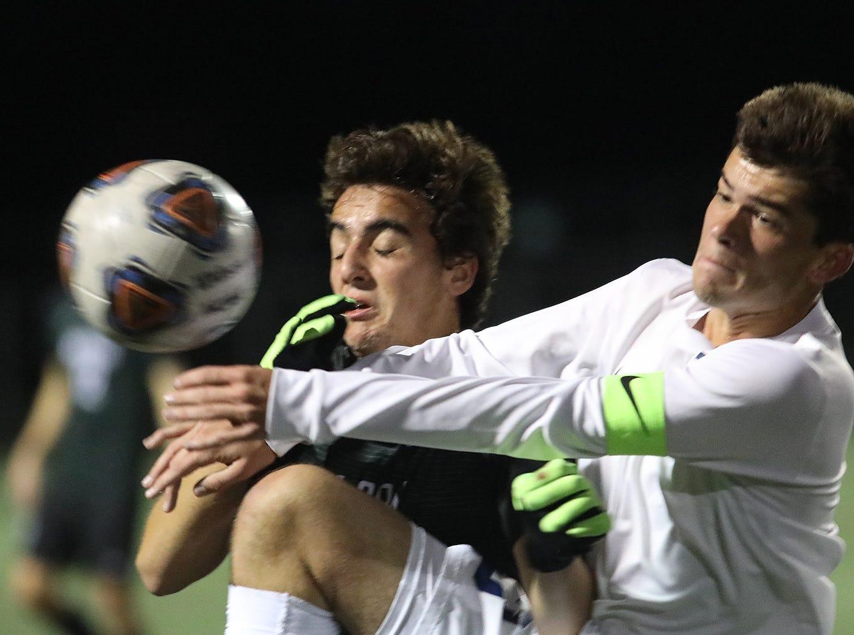 Moeller midfielder Adam Cusmano (13) battles Mason midfielder Micheal  Valcarcel (8)  during their district final.