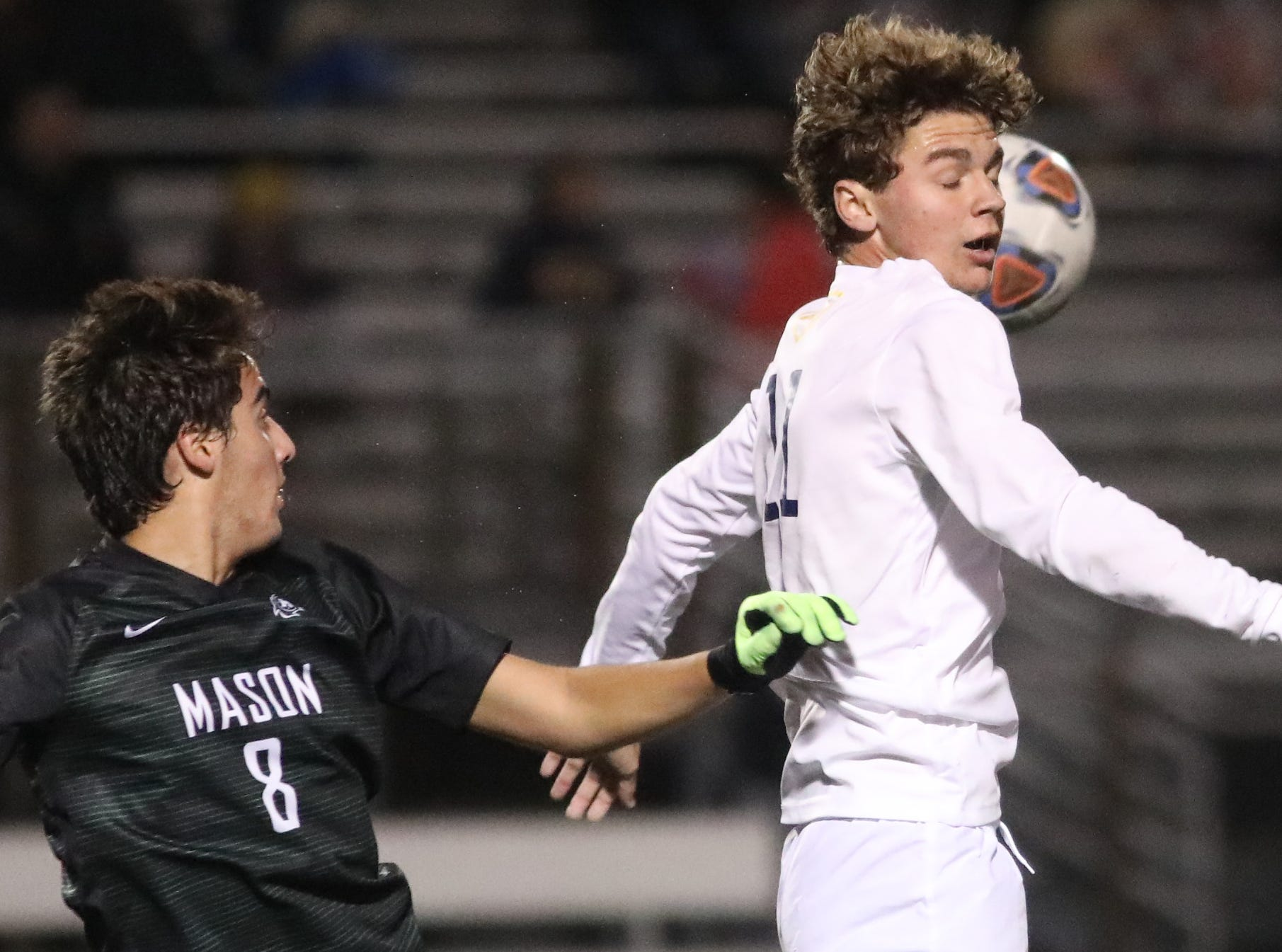 Moeller midfielder Parker Grinstead  battles Mason midfielder  Sebastian Amays for the ball during their district final.