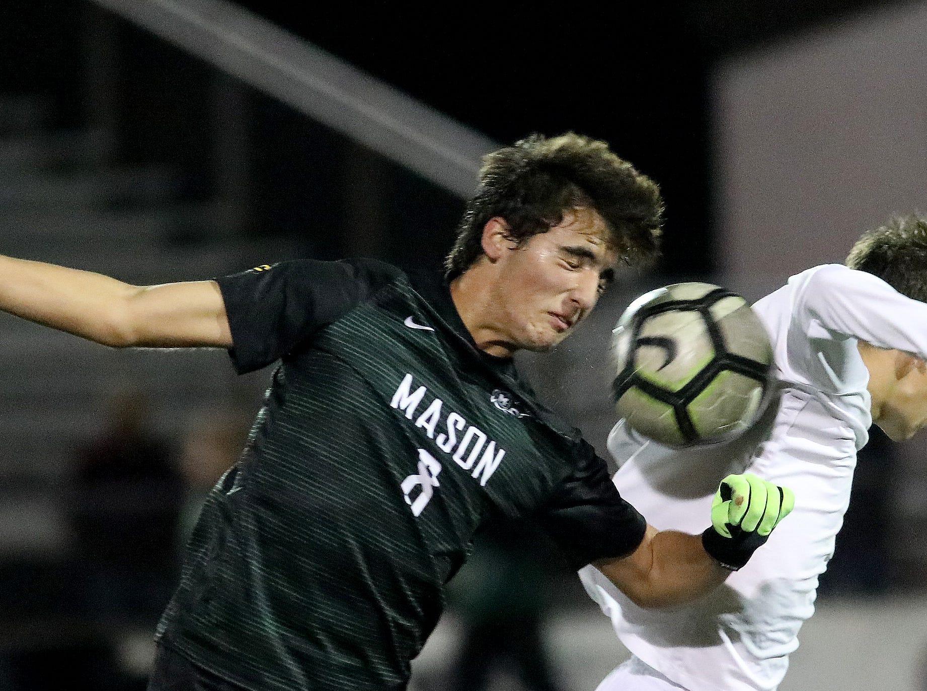 Mason midfielder Sebastian Amaya (8) battles Moeller midfielder Ben Hegge in the district final.