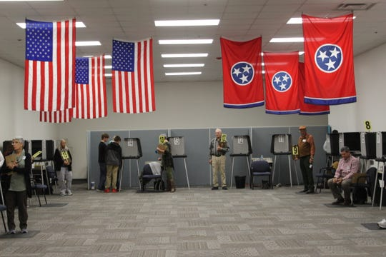 Poll workers waiting by voting booths during early voting in Montgomery County.