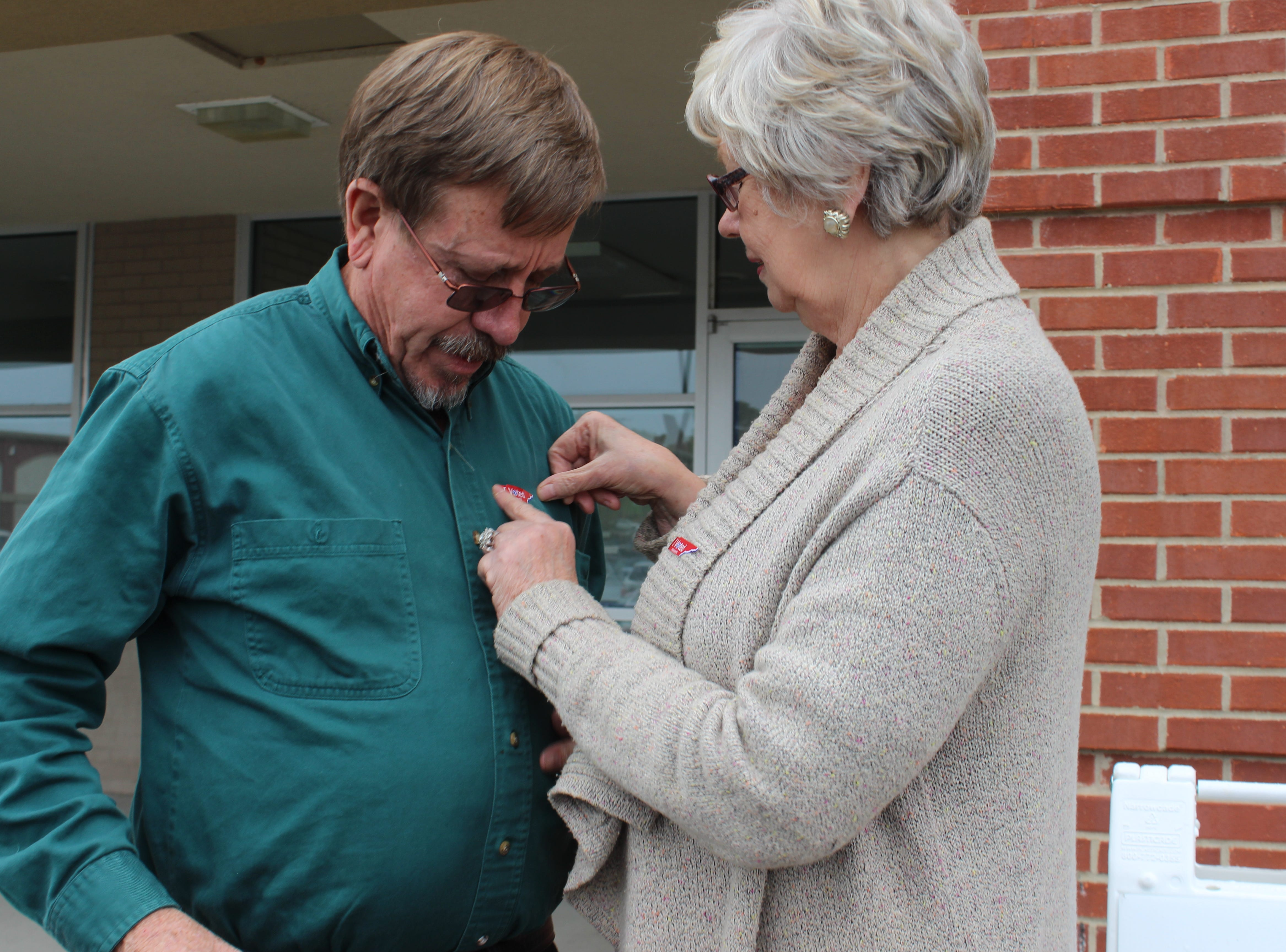 Dr. Larry Harris and Dr. Carmen Reagan affix their voter stickers after casting early ballots in Montgomery County.
