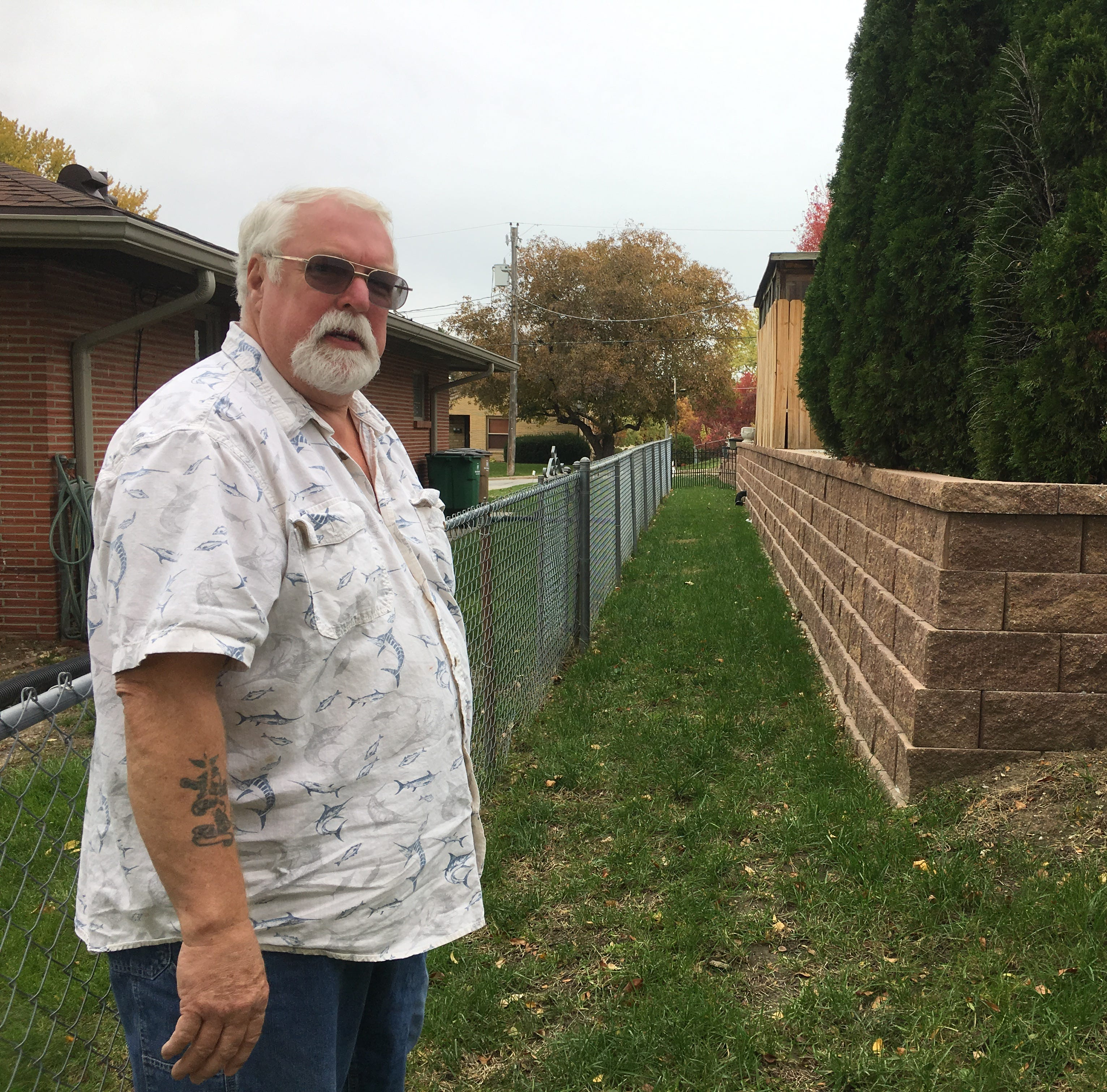 Gary Coil stands near the new retaining wall he...