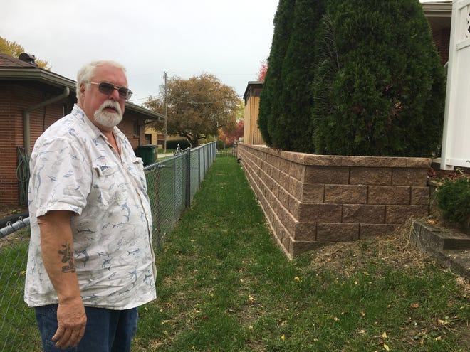 Gary Coil stands near the new retaining wall he built last summer at his Windsor Heights home.