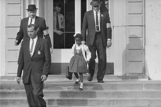 In this Nov. 1960 file photo, U.S. Deputy Marshals, including Charles Burks, top left, escort six-year-old Ruby Bridges from William Frantz Elementary School in New Orleans, La. The first grader was the only black child enrolled in the school, where parents of white students were boycotting the court-ordered integration law and were taking their children out of school.