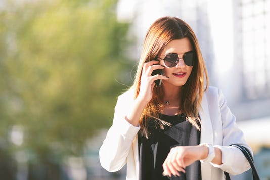 Businesswoman Talking On Phone And Checking Time