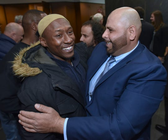 Exonerated Mubarez Ahmed, right, hugs and smiles with friend Tim Abdul-Matin.