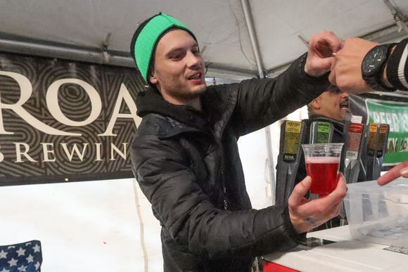 Charles Osberger, southeast territory sales manager for Roak Brewing, hands a festival-goer a glass of Little Saint Nick, the brewer's holiday seasonal Cranberry gose.