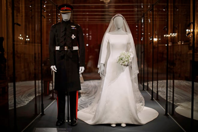 """The wedding dress with a 5-meter-long veil that Meghan the Duchess of Sussex wore and an identical uniform to the specially commissioned one Prince Harry wore at their May 19, 2018, wedding, are displayed as part of the exhibit """"A Royal Wedding: The Duke and Duchess of Sussex"""" in the Grand Reception Room at Windsor Castle in Windsor, near London, England."""