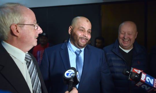 Co-council David Moran, left, and private investigator Scott Lewis, right, share a laugh with Mubarez Ahmed, center, as they talk to the media.
