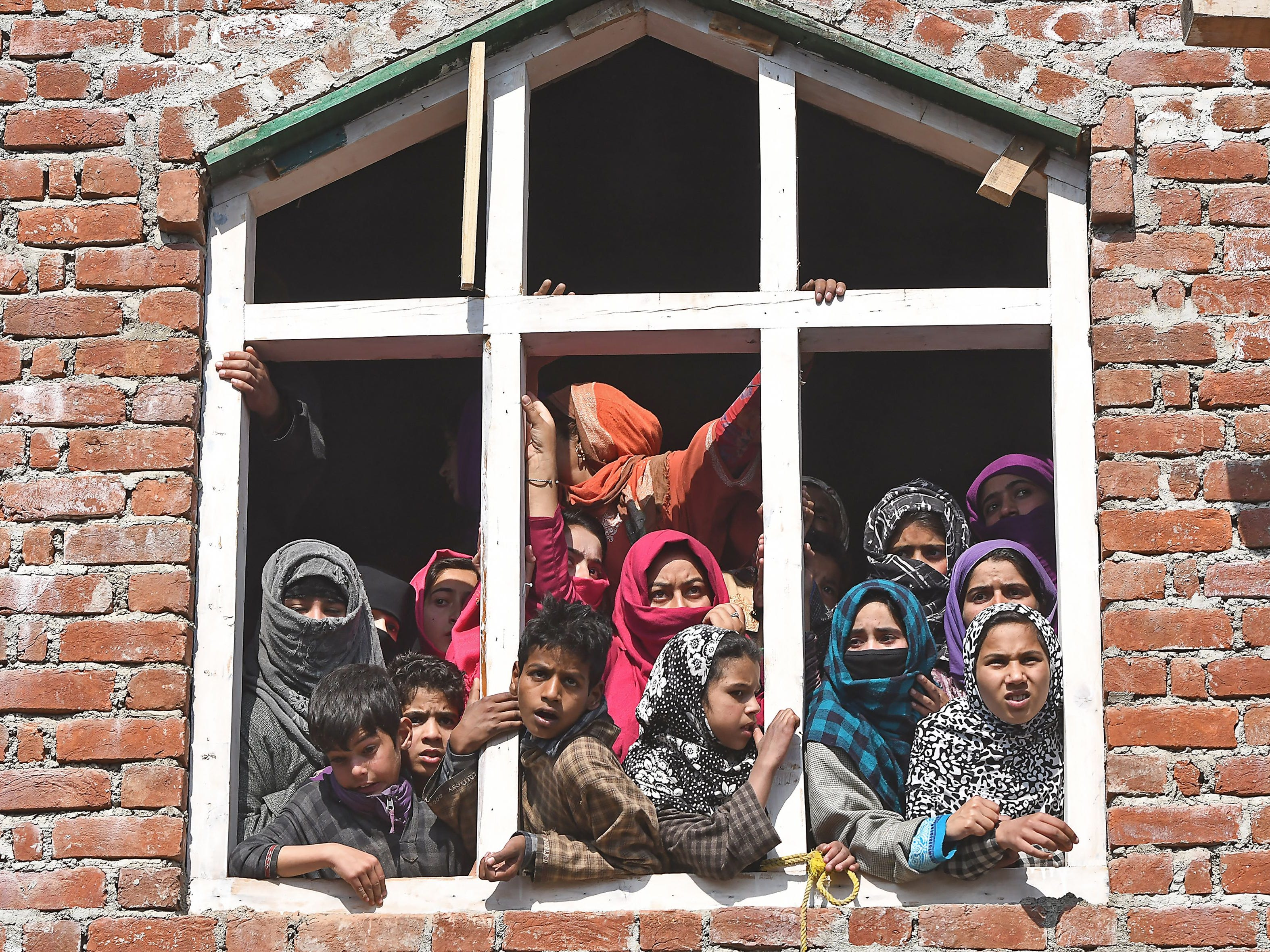 Villagers watch a funeral procession for militant Sahir Ahmed, who was killed in a gun battle with Indian soldiers, in Arwani village, in the southern part of Kashmir on Oct. 26, 2018.