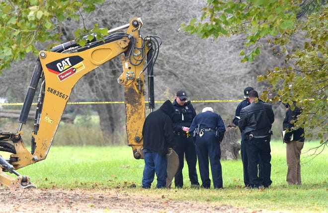 Law enforcement officials look down in the hole Friday as they investigate the discovery of possible skeletal remains at Stoepel Park in Detroit.