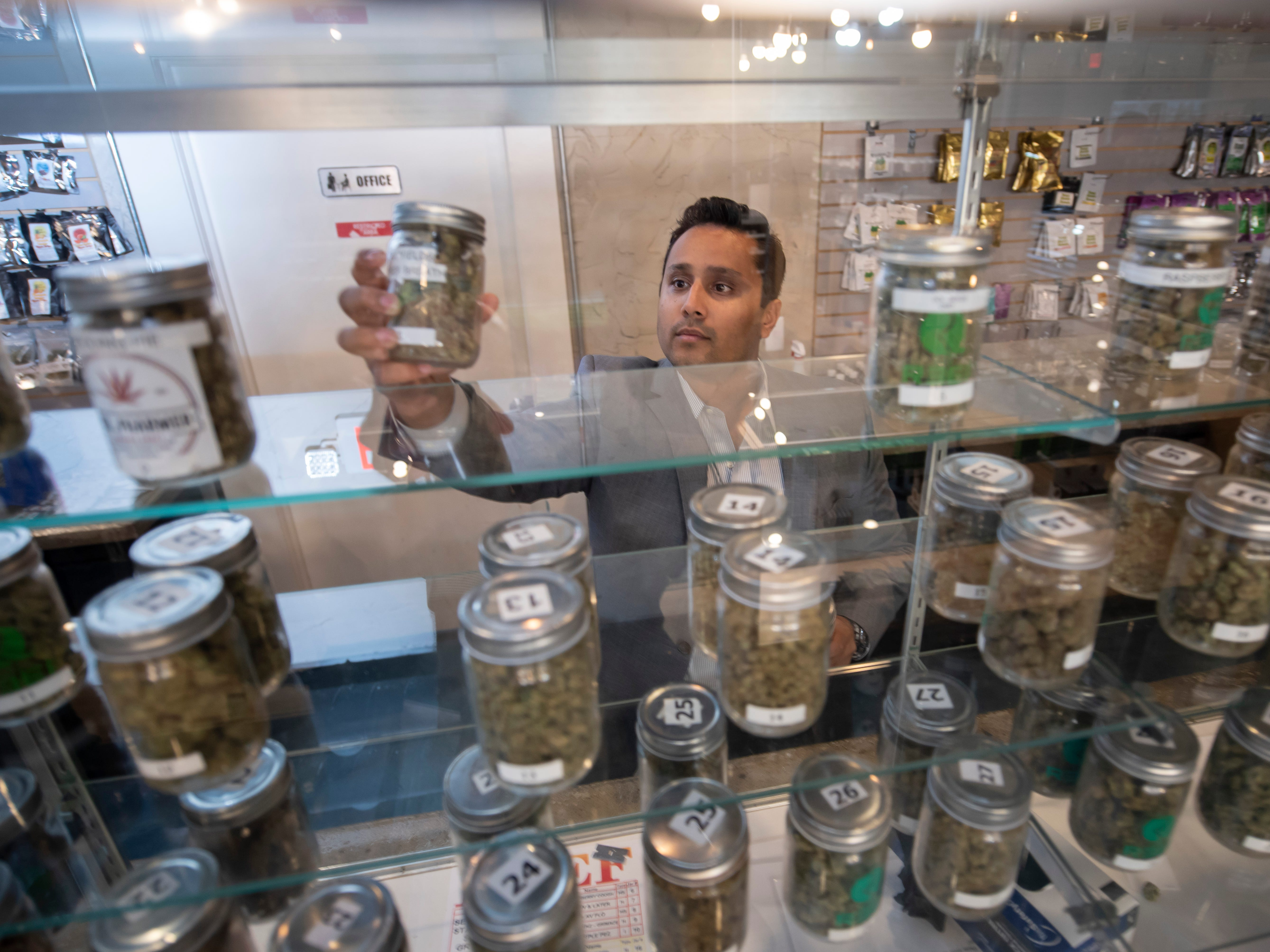 Rush Hasan, operations and business development for The Reef marijuana dispensary, pulls down a jar of product at the Eight Mile location in Detroit.