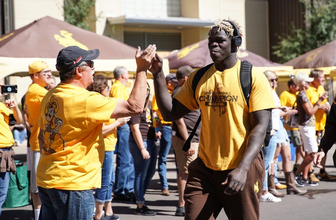Sep 15, 2018; Laramie, WY, USA; Wyoming Cowboys defensive tackle Youhanna Ghaifan (right) greets fans before game against the Wofford Terriers at Jonah Field War Memorial Stadium. Mandatory Credit: Troy Babbitt-USA TODAY Sports