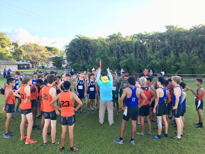 Runners listen to race instructions before the Class 2A-District 12 meet Friday at Bishop Verot High School.