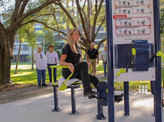 Gulf Coast Village wellness director Lori Robbins demonstrates an exercise station along the 'Faith and Fitness Trail'.