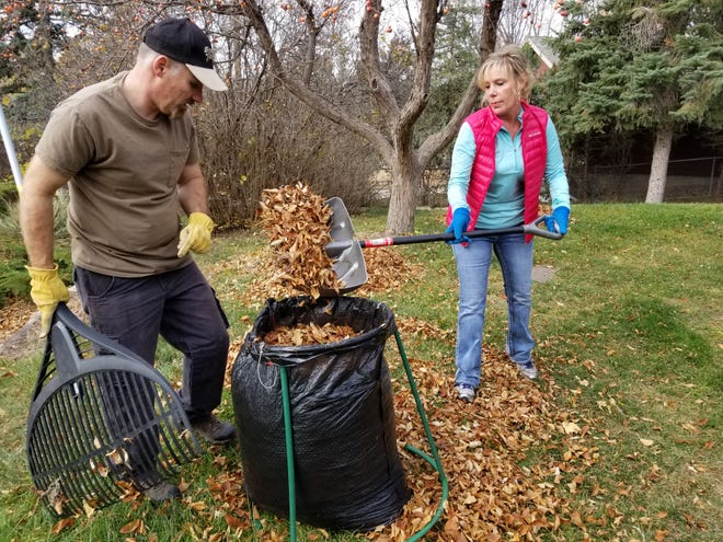 Trish Foss,  part of a team from Kelley Imaging, helps rake leaves during the United Way's Day of Caring.