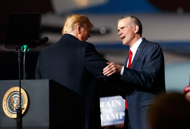 This Thursday, Oct. 18, 2018 file photo shows President Donald Trump and Montana State Auditor Matt Rosendale, who is running against Sen. Jon Tester, D-Mont., shaking hands during a campaign rally at Minuteman Aviation Hangar in Missoula, Mont. The president is holding another rally in Montana in Bozeman on Saturday, Nov. 3.