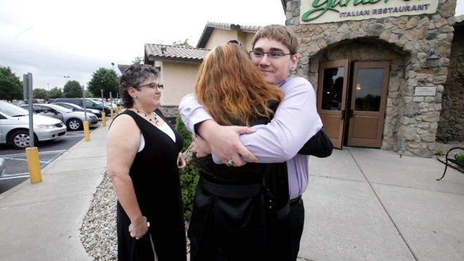Manual High School senior Brent Jones hugs his birth mother, Elizabeth Jones-Gati, for the first time outside of the Olive Garden in Avon Tuesday, May 18, 2010, with the woman who raised him, Kim Roberson, nearby.  Until contact was made with Jones-Gati, Jones struggled to obtain his birth certificate and had no social security number, which left him with little options.