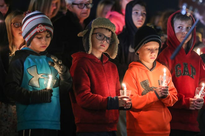From left, Hoosier Road Elementary fourth grader Joshua Turner, third graders Cale Beattie, Simon Turner and Henry Skeen stand together during a vigil remembering teachers Kristal Sergi and Frank Sergi at the elementary school in Fishers, Ind., Thursday, Oct. 25, 2018. Kristal, a preschool teacher at Hoosier Road, and Frank, an art teacher at Fall Creek Intermediate, were found dead in their Fishers home Wednesday night, Oct. 24, 2018. The couple was amidst divorce proceedings and the police said they are not looking for a suspect in the deaths.