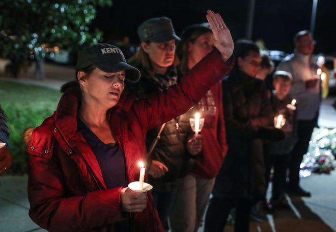 At left, Beth Comer raises her hand in prayer while worship songs are performed during a vigil remembering teachers Kristal Sergi and Frank Sergi, at Hoosier Road Elementary in Fishers, Ind., Thursday, Oct. 25, 2018. Kristal, a preschool teacher at Hoosier Road, and Frank, an art teacher at Fall Creek Intermediate, were found dead in their Fishers home Wednesday night, Oct. 24, 2018. The couple was amidst divorce proceedings and the police said they are not looking for a suspect in the deaths.