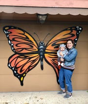 The monarch butterfly mural by artist Jules Muck is a symbol of the transformation and joy Kelsey Carrier experienced when she had her first child, Arlo. The mural is on Carrier's garage in Little Flower.