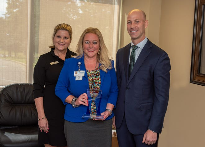 West Tennessee Healthcare's Dr. Lisa Piercey (center) accepts a commemorative plaque from LHC Group's Brach Myers and Tish Robinson.