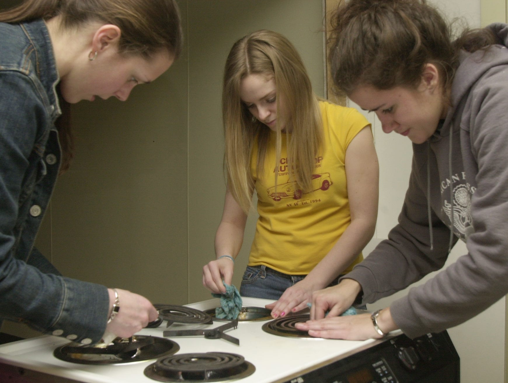 Cleaning a stove for resale in the new Habitat for Humanity second-hand store in Oak Ridge are, from left, Anderson County High School student, Charlsea Cardwell, Clinton High student Kari Leonard and Jessie Coulter, a student at Salem College in Winston-Salem, NC.