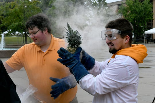UTK physics students Chase Board, right, and Peter TarlŽ get another piece of fruit frozen in liquid nitrogen to smash with sledgehammers Friday, October 26, 2018.