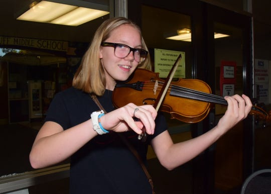 Braelyn Lemere, 13, makes sure her fiddle is in tune.