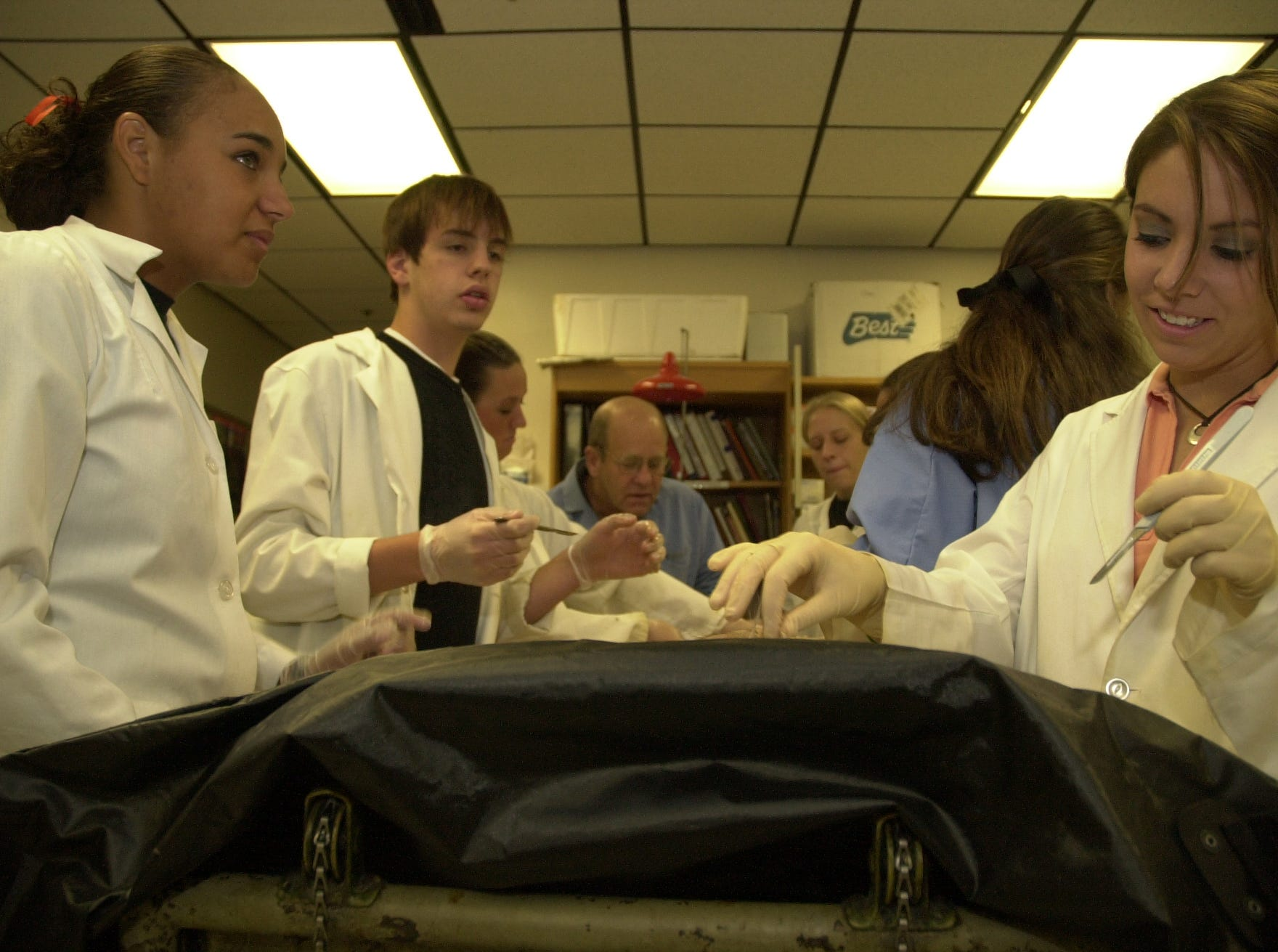 Physiology students at Clinton High School dissect a human cadaver with the help of their teacher, Dr. Harry ``Whitey'' Hitchcock, in background.  From left: Shere Ramsey, Tyler Morrow, Rachel Geier, Hitchcock, Chantal Mings, Amanda Hatton, back to camera, and Kaylee Webster.