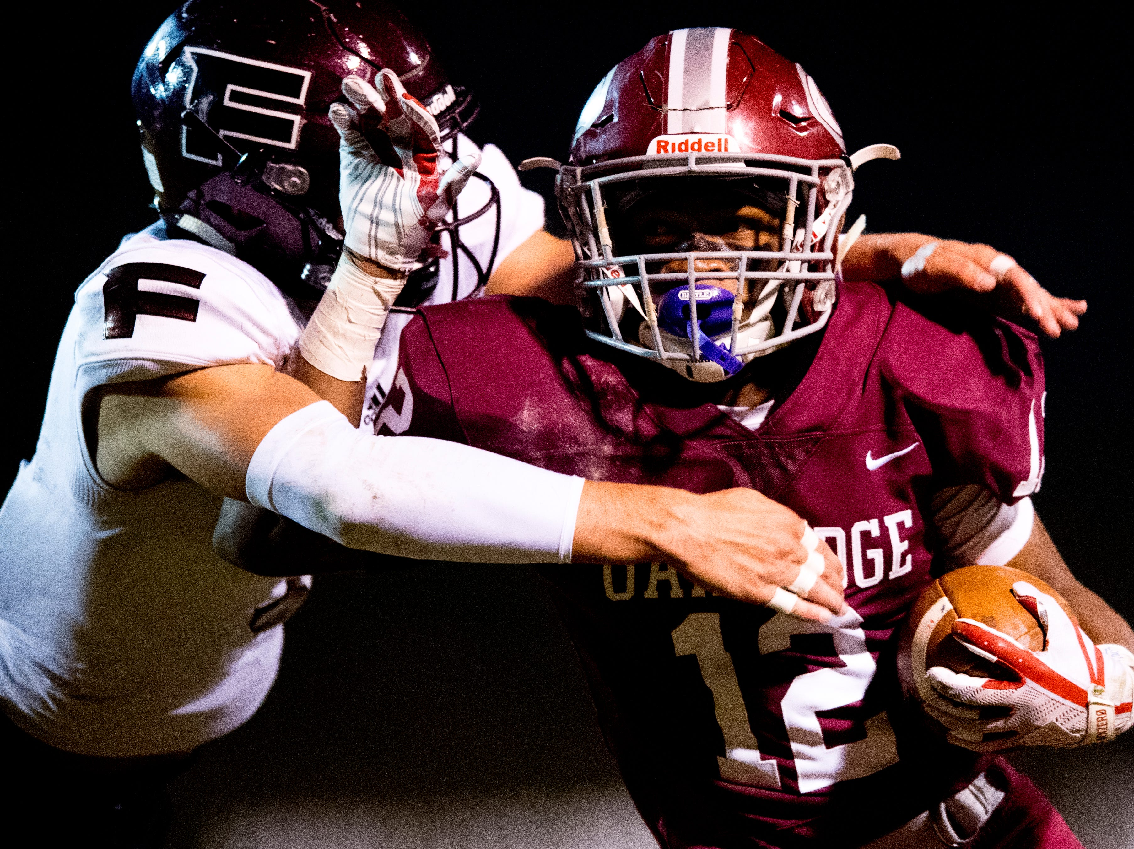 Oak Ridge's Kai'Reese Pendergrass (12) is attacked by Fulton's Tommy Sweat (9) during a football game between Oak Ridge and Fulton at Blankenship Field in Oak Ridge, Tennessee on Thursday, October 25, 2018.