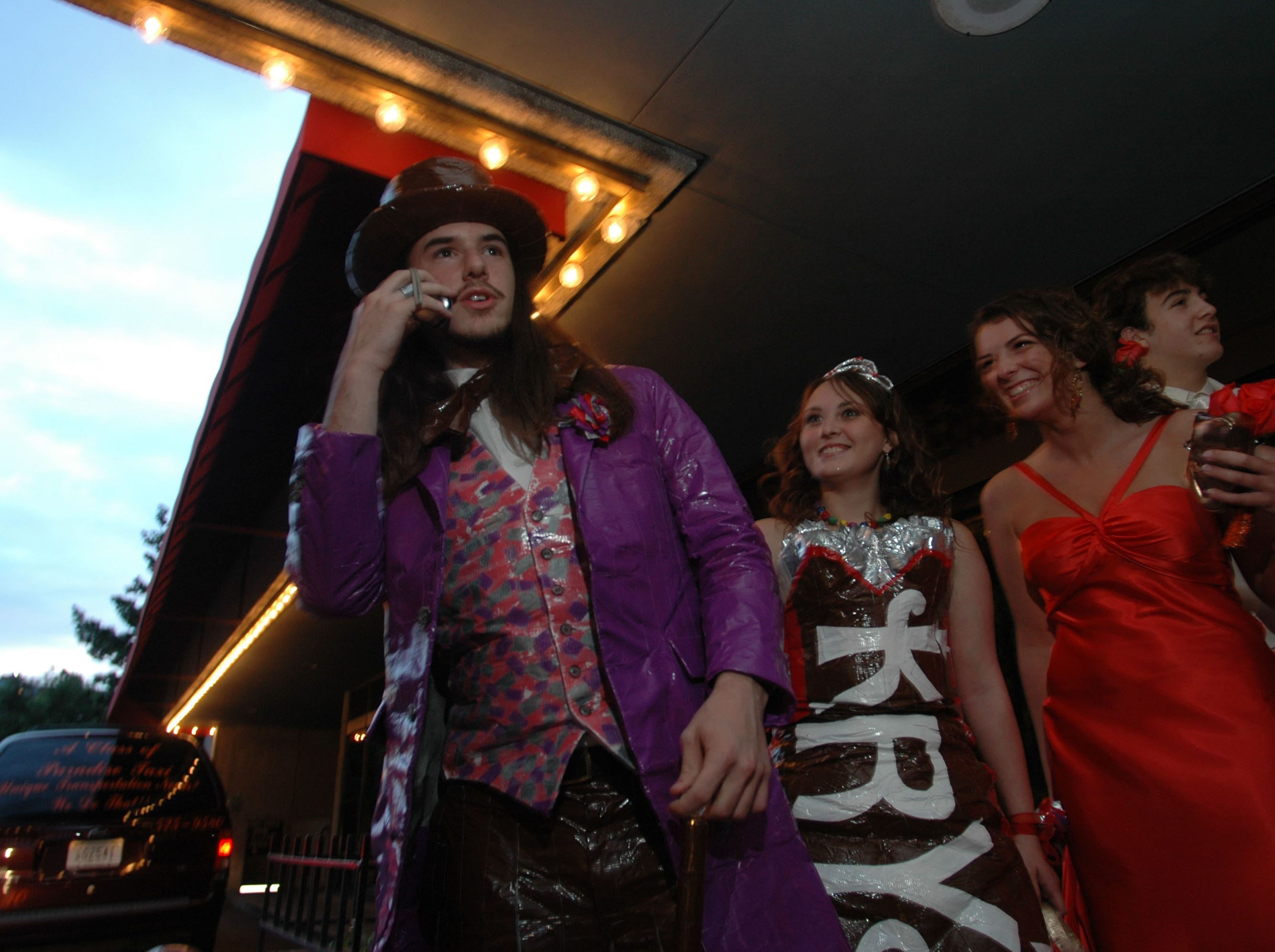 T.J. Daugherty, left, talks to a friend on his cell phone while is date Krystle Gutman, and their friends Leslie Spitzer and her date Dylan Ryan wait for Elvis Impersonator Ray E. Robbins to escort them into to the Clinton High School Prom Saturday night at the Crowne Plaza Hotel. Gutman and Daugherty made their outfits using different color duct tape made to resemble the original Willy Wonka and the Chocolate Factory characters. 05/13/2006.