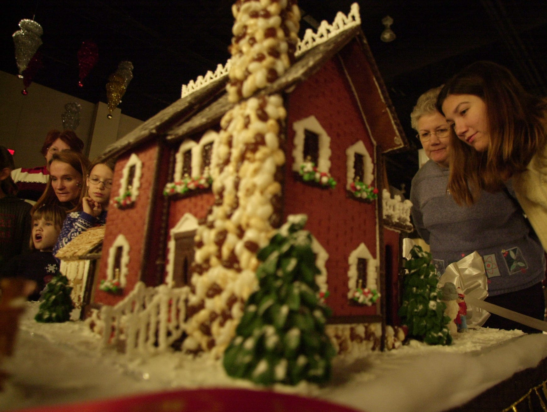 Katie Gillespie, far right, and Cathy Taylor, second from right, check out a gingerbread house made by Greenback High School students  during the 2004 Fantasy of Trees at the Knoxville Convention Center Saturday.