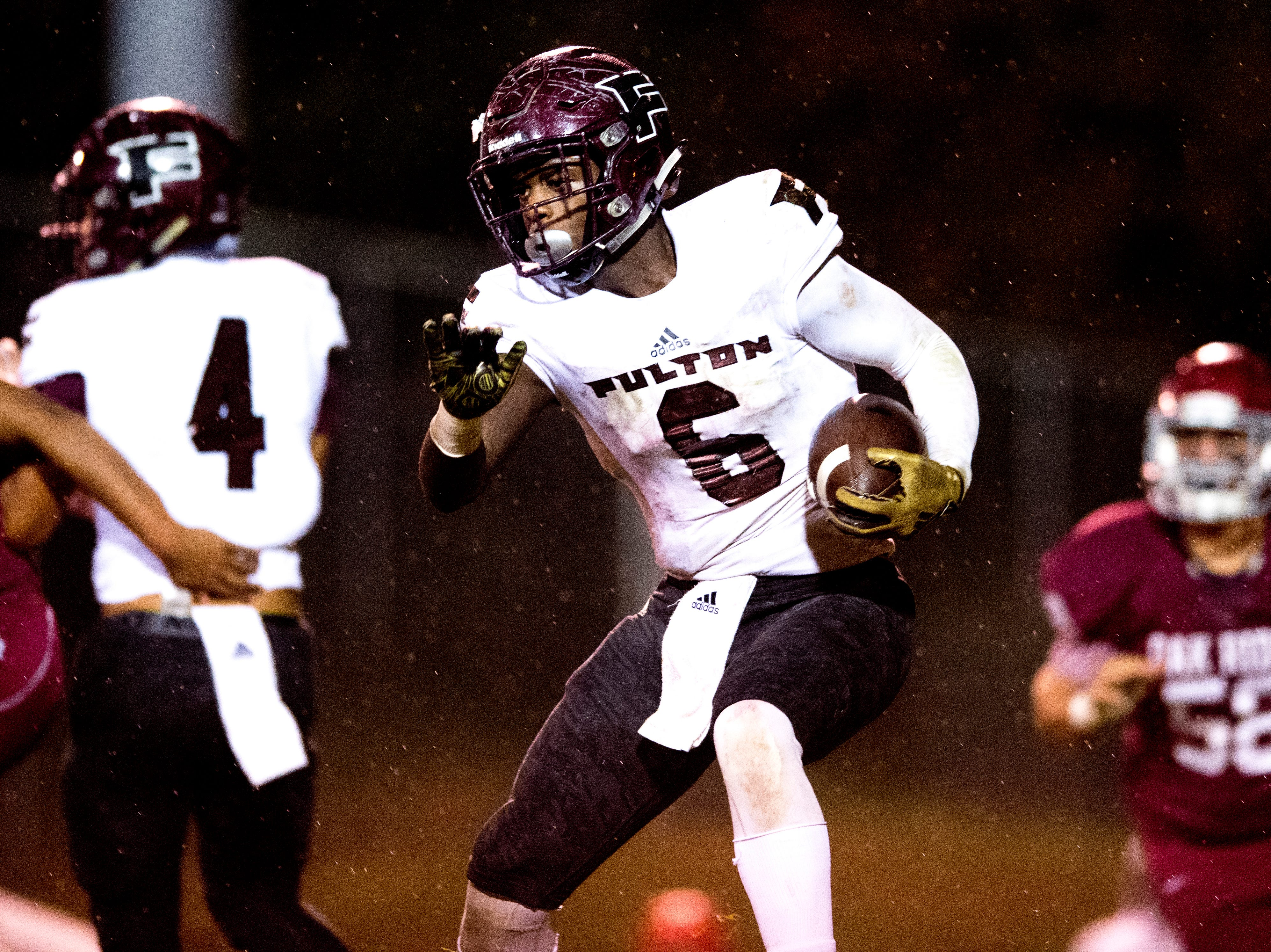 Fulton's DeShawn Page (6) runs with the ball through the rain during a football game between Oak Ridge and Fulton at Blankenship Field in Oak Ridge, Tennessee on Thursday, October 25, 2018.