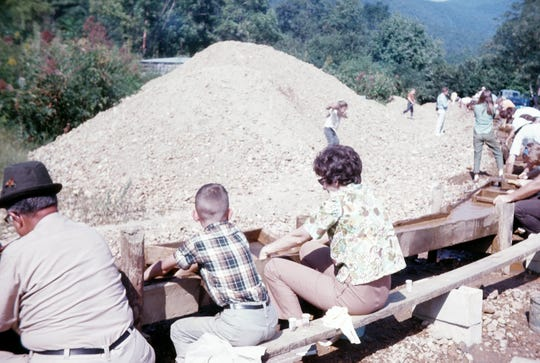 Craig McClung, center, then 10 years old, pans for small gems with his mother, Frances McClung, on a family rock hunting trip to Franklin, N.C.
