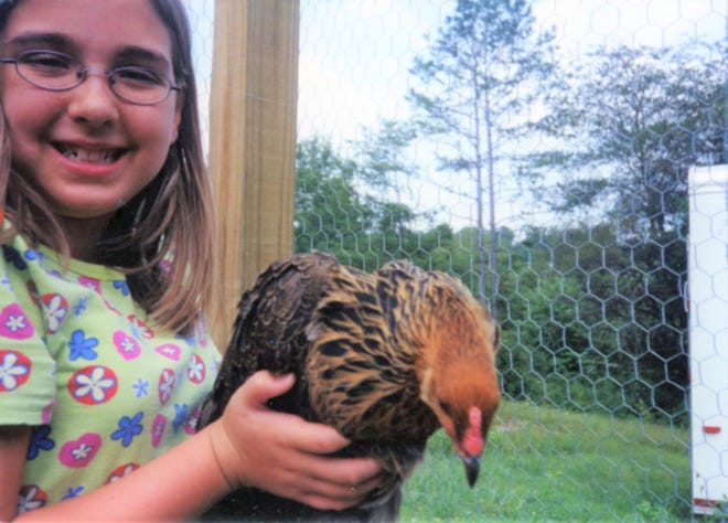 Business reporter Cortney Roark as an 11-year-old holds Speckles the chicken, who laid green eggs.