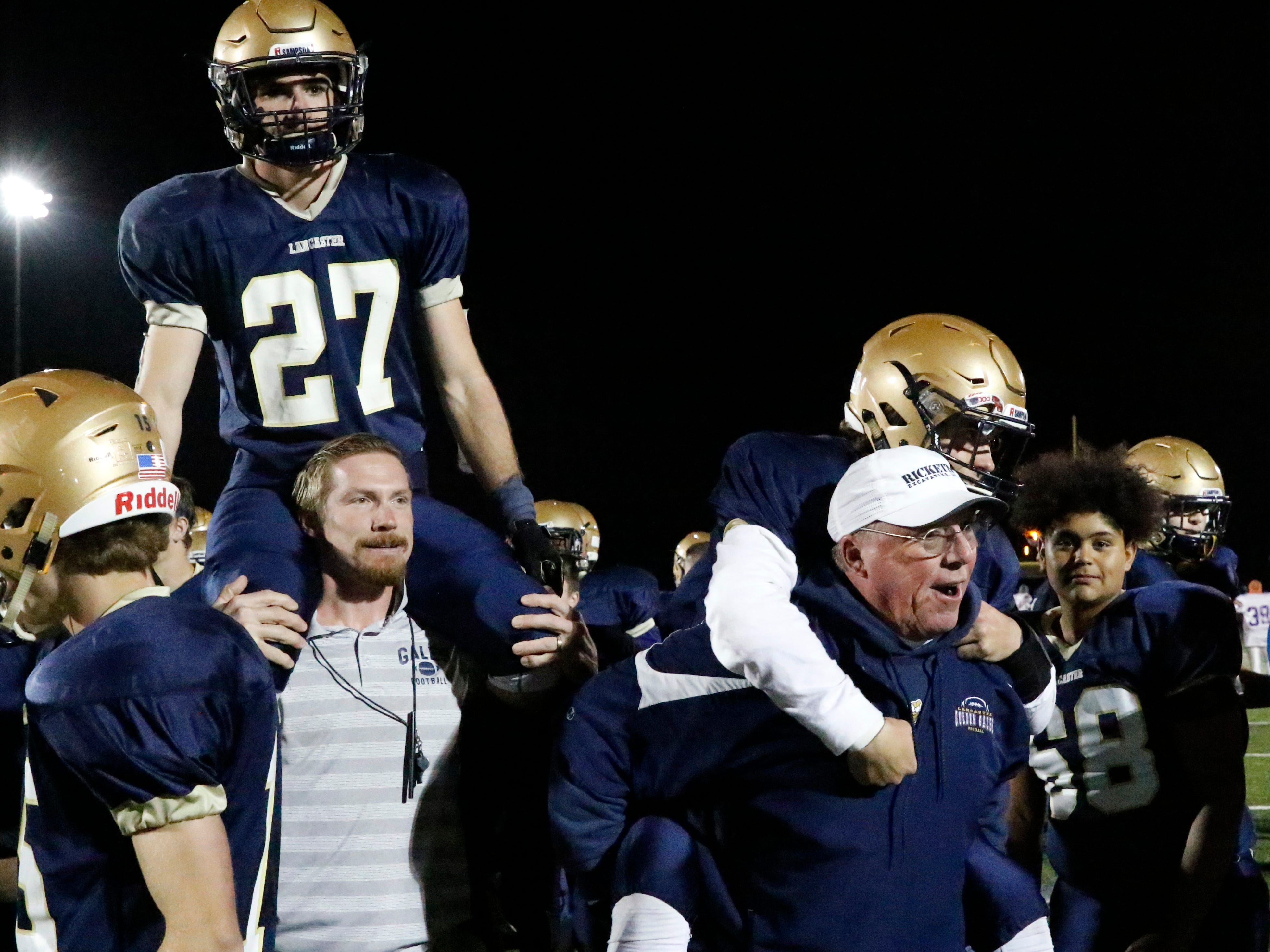 Lancaster football coach Rob Carpenter, right, carries senior Tyler Monk off the field on his back while assistant coach Jon Carpenter carries senior A.J. Cook after Thursday night's game, Oct. 25, 2018, at Fulton Field in Lancaster. The Golden Gales lost the game, 28-7 to Reynoldsburg. The teams ended the regular season as co-champions of the Ohio Capital Conference-Ohio Division.