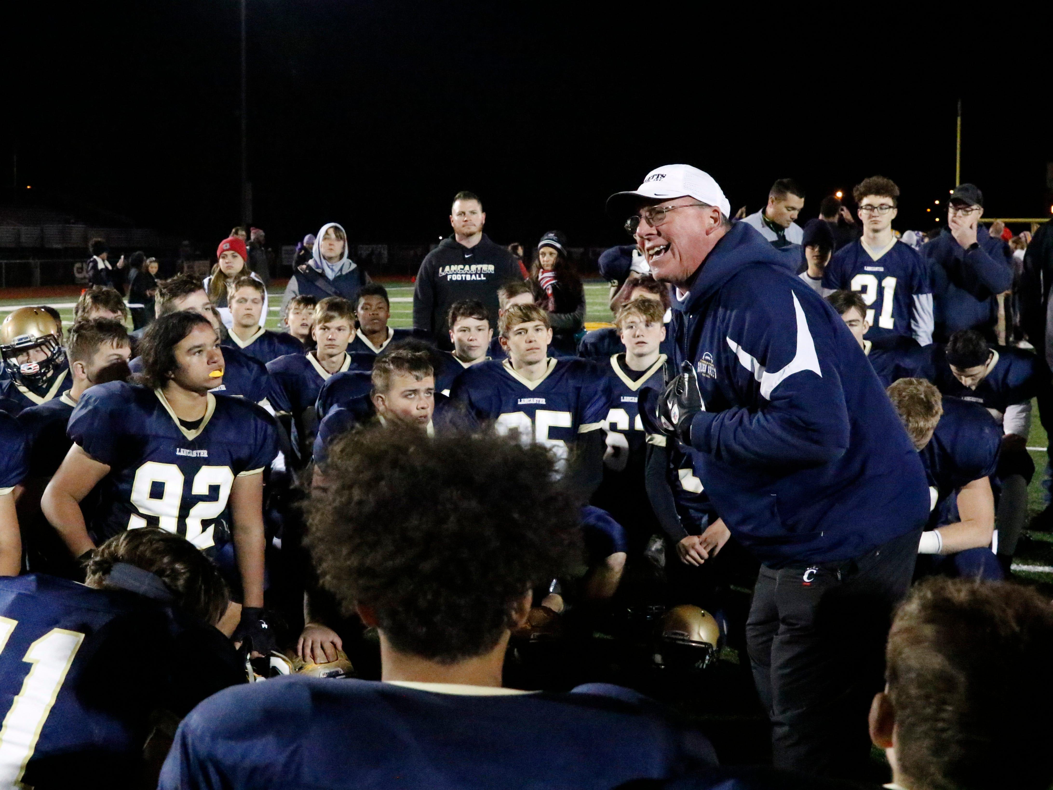 Lancaster football coach Rob Carpenter, right, talks to his team after a 28-7 loss to Reynoldsburg Thursday night, Oct. 25, 2018, at Fulton Field in Lancaster.