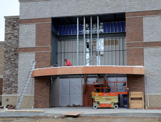 Workers construct the facade of the front entrance of the soon-to-open Emagine Hartland movie theater, Friday, Oct. 26, 2018.