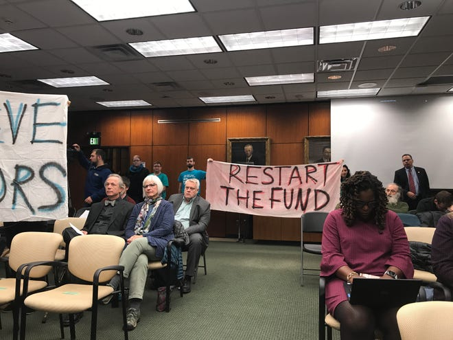Protesters at the Michigan State University Board of Trustees meeting on Friday, Oct. 26, 2018 held up signs, including one demanding for the unfreezing of its Healing Assistance Fund. The fund can be accessed by Larry Nassar survivors starting Sept. 1 under the new name Counseling and Mental Health Services Fund.