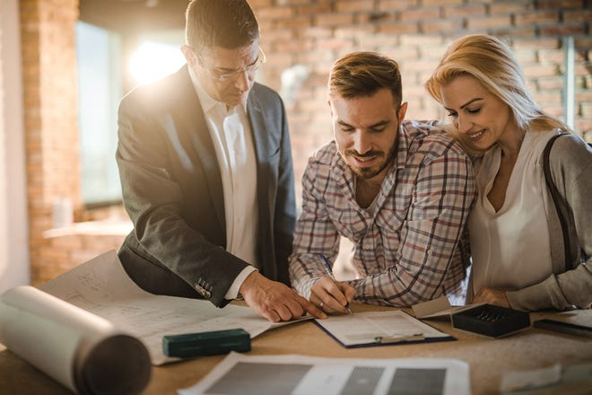 Mid adult investor showing young couple where to sign the contract for buying a house.