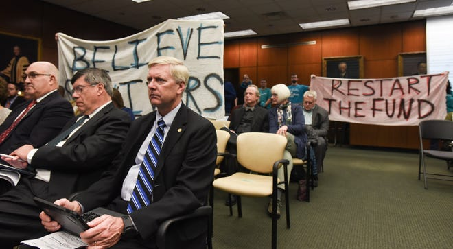 """A handful of protesters hold up signage directed at the MSU Board of Trustees, Friday, Oct. 26 2018, during the Board of Trustees meeting at the Hannah Administration Building on the campus of MSU.  The one on the left reads """"Believe Survivors."""""""