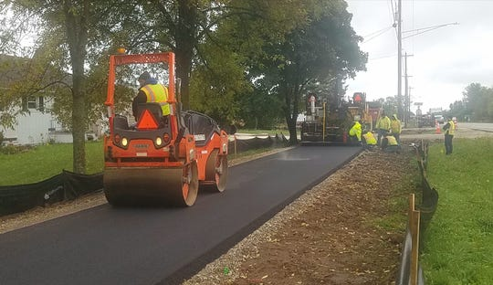 Vinton Construction workers pave a portion of the new Raider Trail in Two Rivers.
